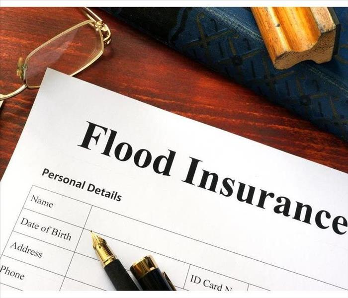 "There is a desk with eye glasses a fifty dollar bill and a paper that says ""Flood Insurance"""