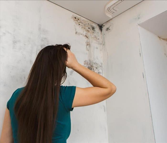 Woman holding her head, watching the ceiling of her house that is damp and with mold