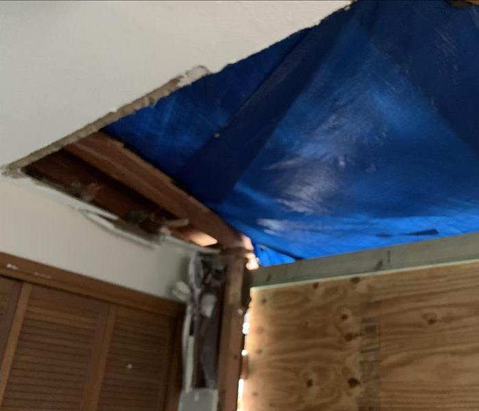 A blue tarp and wood covering holes in a home